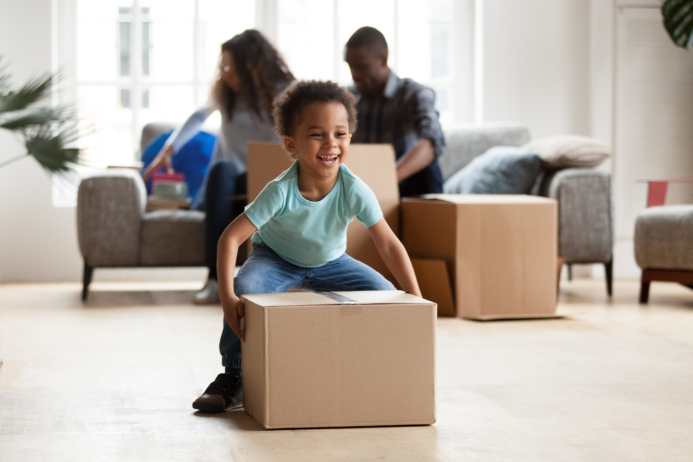 Couple sitting unpacking boxes on moving day and young boy picking up a moving box